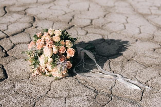 Bouquet de mariée sur fond de terre craquelée