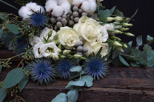 Bouquet de mariée d'hiver de roses blanches, de coton et d'eringium sur fond noir. le bouquet de la mariée.