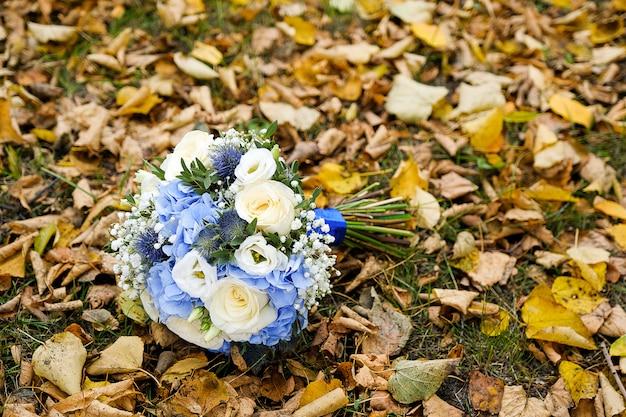 Le bouquet de la mariée joliment décoré de différentes couleurs vives et de feuilles vertes se trouve sur l'herbe d'automne. thème de mariage.