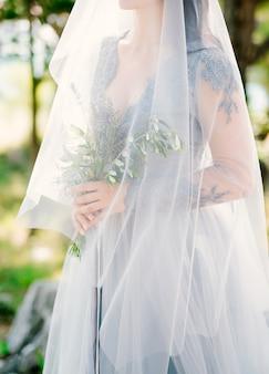 Bouquet de mariée lavande dans les mains de la mariée sous voile en robe bleu pâle