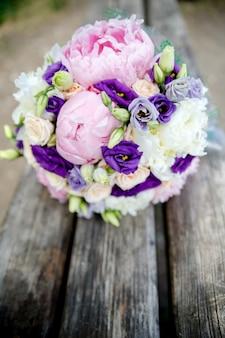 Bouquet de mariée de mariées de pivoines et rose sur fond de bois