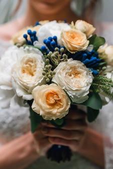 Bouquet de mariée de pivoines blanches et de roses jaunes entre les mains de la mariée