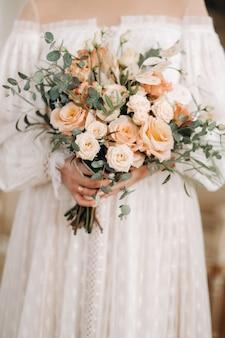 Bouquet de mariée avec des pivoines dans les mains de la mariée sous le voile.matin de la mariée.