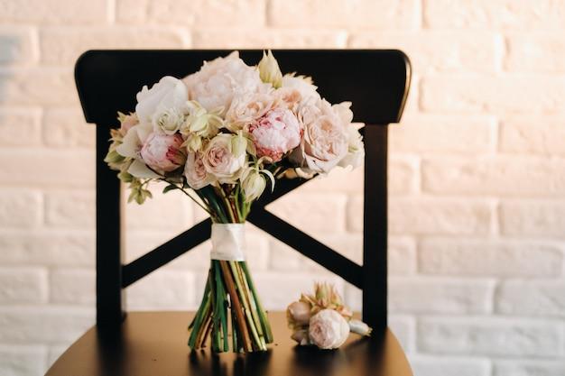 Bouquet de mariée avec des pivoines et des roses sur une chaise et une boutonnière.la décoration au mariage.