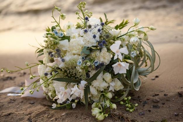 Bouquet de mariée sur la plage au coucher du soleil gros plan