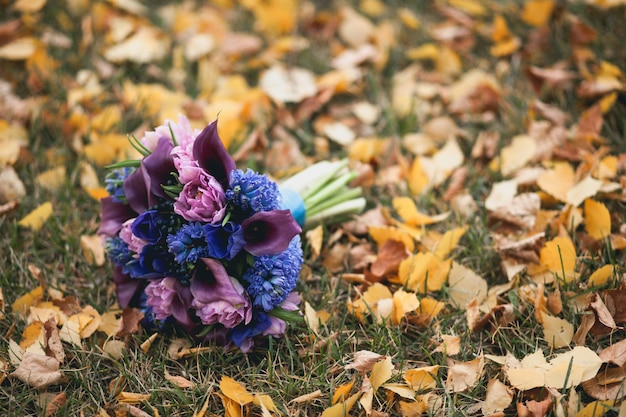 Le bouquet de la mariée repose sur l'herbe d'automne.