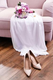 Bouquet de mariée, robe de demoiselle d'honneur et chaussures dans la chambre