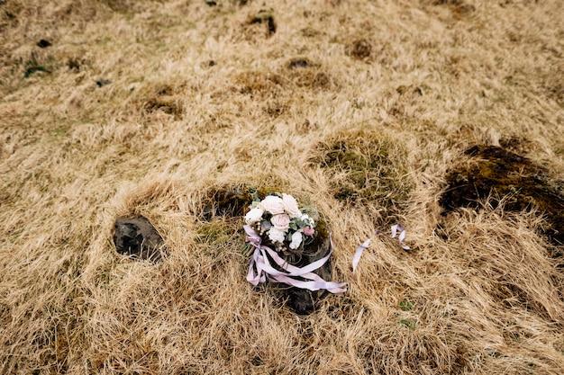 Bouquet de mariée de roses blanches brunia et leucadendron au sol dans l'herbe séchée en islande