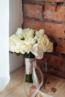 Bouquet de mariée de roses blanches sur un espace de mur de brique