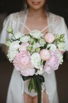 Bouquet de mariée de roses blanches et de pivoines entre les mains de la jeune belle mariée le matin avant la cérémonie de mariage