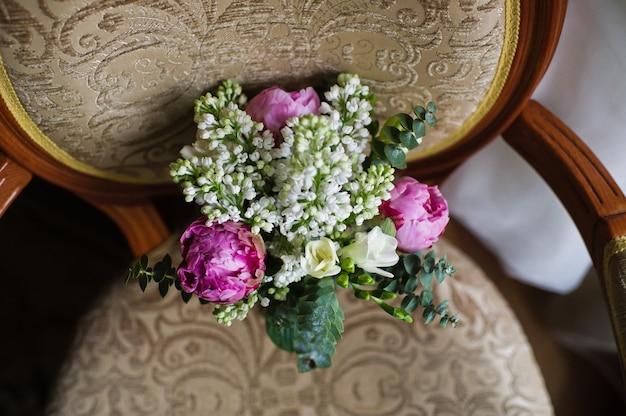Bouquet de mariée de roses blanches et de pivoines violettes.