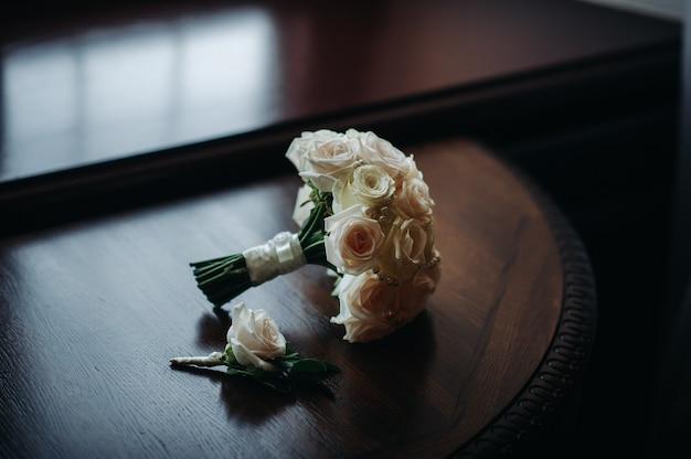 Bouquet de mariée avec roses et boutonnière.la décoration au mariage.