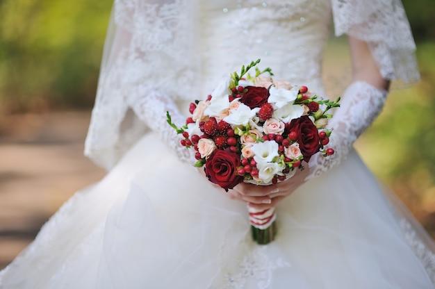 Bouquet de mariée de roses entre les mains de la mariée