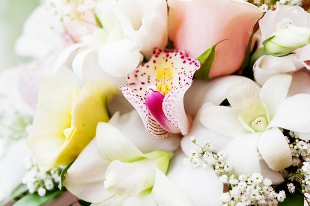 Bouquet de mariée avec des roses, des fleurs de gypsophila et des orchidées.