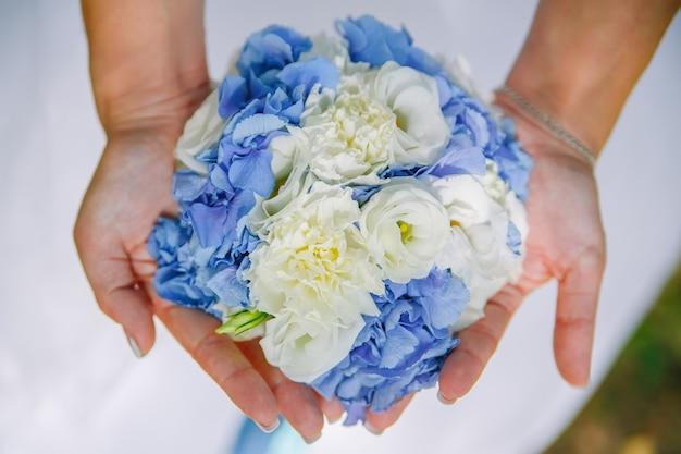Bouquet de mariée de roses et de fleurs d'hortensia dans les mains de la mariée