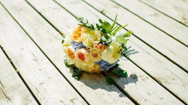 Un bouquet de mariée de roses jaunes et blanches sur une planche en bois blanche