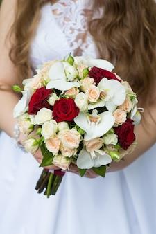 Bouquet de mariée de roses et d'orchidées entre les mains de la mariée