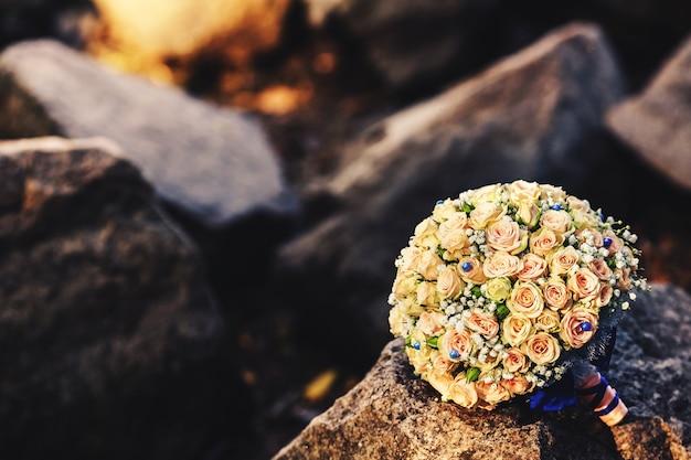Un bouquet de mariée de roses pastel avec des strass bleus et un ruban se trouve sur les pierres