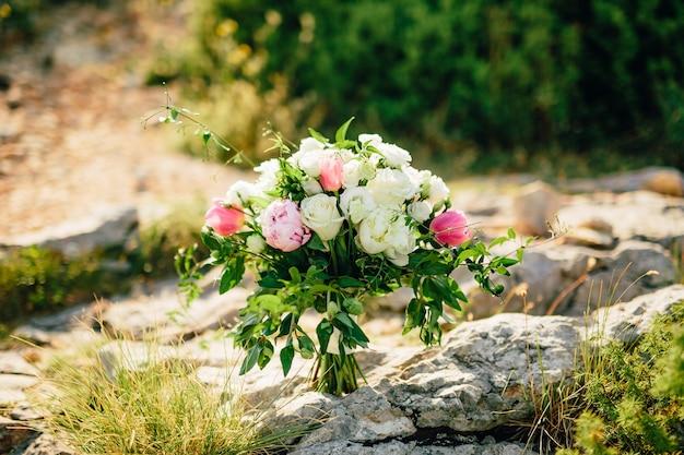Bouquet de mariée de roses et de pivoines sur les rochers mariage à mont