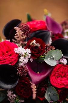 Bouquet de mariée rouge. anneaux de mariée dans le parc.