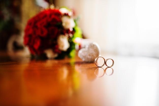 Bouquet de mariée rouge avec des anneaux sur une table en bois