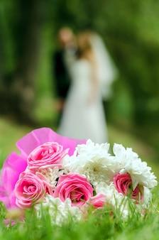 Bouquet de mariée sur la silhouette floue d'une mariée avec le marié