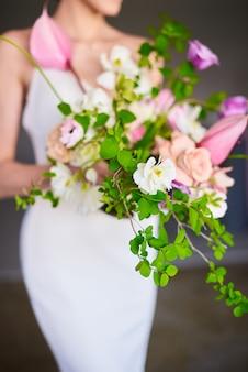 Bouquet de mariée stylé entre les mains de la mariée