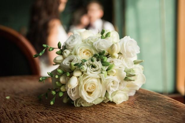 Bouquet de mariée sur une table en bois. bouquet de mariée de freesia et de roses