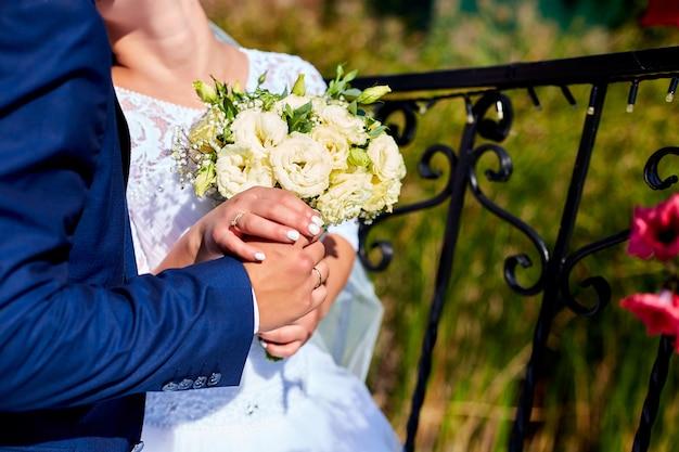 Bouquet de mariée tenant dans les mains d'un couple.