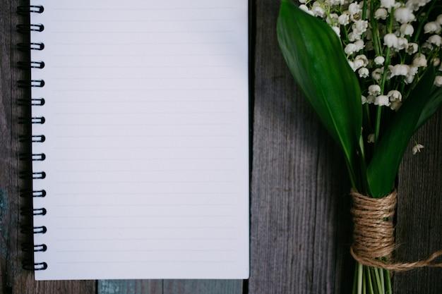 Bouquet de muguet et cahier sur table en bois