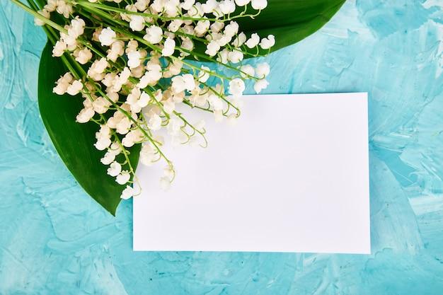 Bouquet de muguet près de carte postale, papier vide.