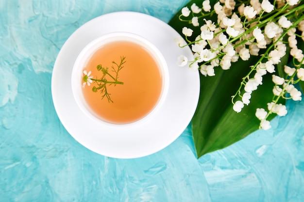 Bouquet de muguet et tasse de thé à la camomille.