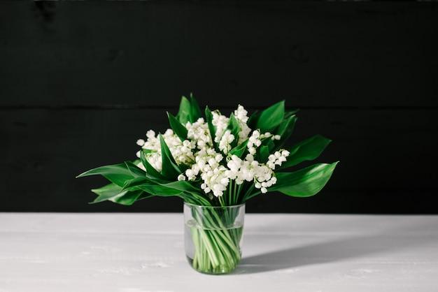 Bouquet de muguets sur un fond en bois blanc et noir