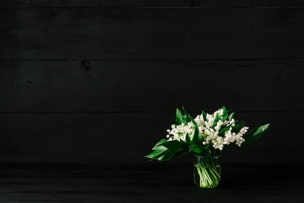 Bouquet de muguets sur un fond en bois noir