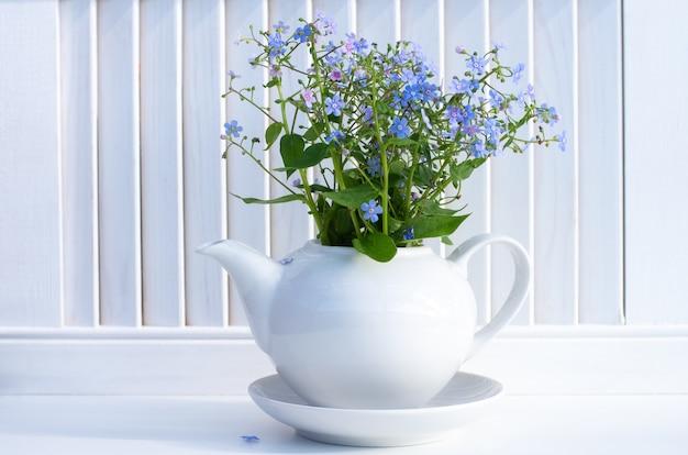 Un bouquet de myosotis bleus dans une théière en céramique blanche