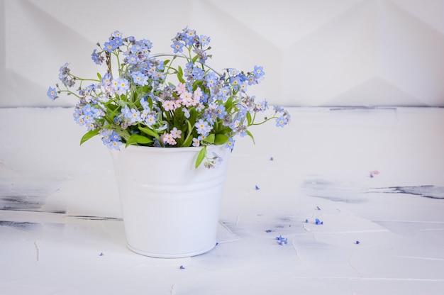 Bouquet de myosotis dans un seau en métal sur blanc