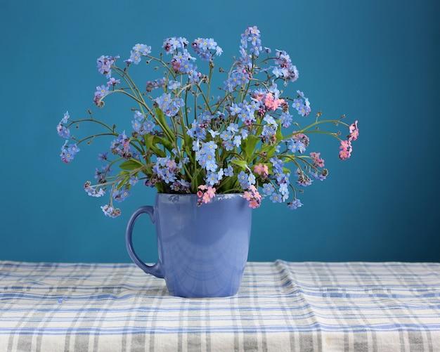 Bouquet de myosotis sur la table sur fond bleu.