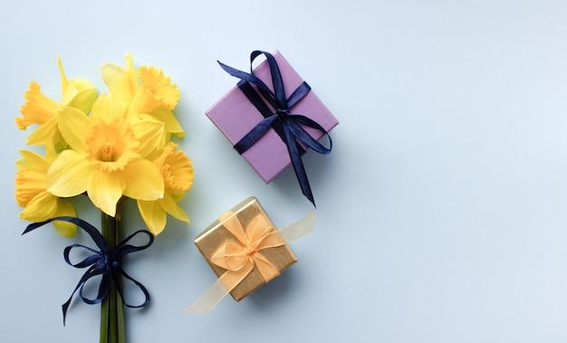 Bouquet de narcisse avec des cadeaux sur fond bleu vue de dessus à plat la journée internationale de la femme le 8 mars carte de vacances avec des fleurs place pour le texte