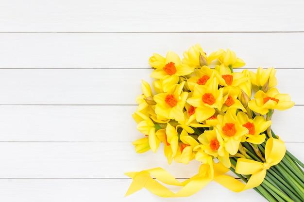 Bouquet de narcisse de printemps frais décoré de ruban sur un mur en bois blanc. vue de dessus, copie