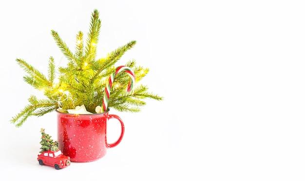 Bouquet de noël dans une tasse rouge en épicéa vivant et décorations et accessoires de fête, jouets pour l'arbre de noël, bonbons. nouvel an, ambiance festive, fleuriste sur fond blanc avec espace de copie