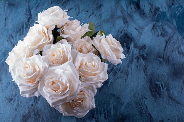 Bouquet de nombreuses roses blanches posées sur bleu.