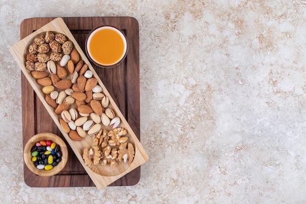 Bouquet de noyaux de noix sur une plaque en bois avec du thé chaud