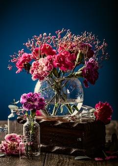 Bouquet d'oeillet rose dans un vase en verre sur une surface bleu foncé. fête des mères, carte de voeux d'anniversaire. copier l'espace