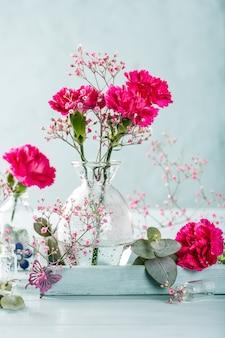 Bouquet d'oeillet rose dans un vase en verre sur une surface en bois turquoise clair. fête des mères, carte de voeux d'anniversaire. copier l'espace