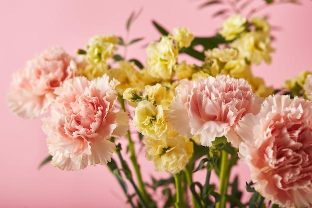 Bouquet d'oeillets roses et de matthiola jaune avec concept de conception de branches vertes de voeux de vacances...