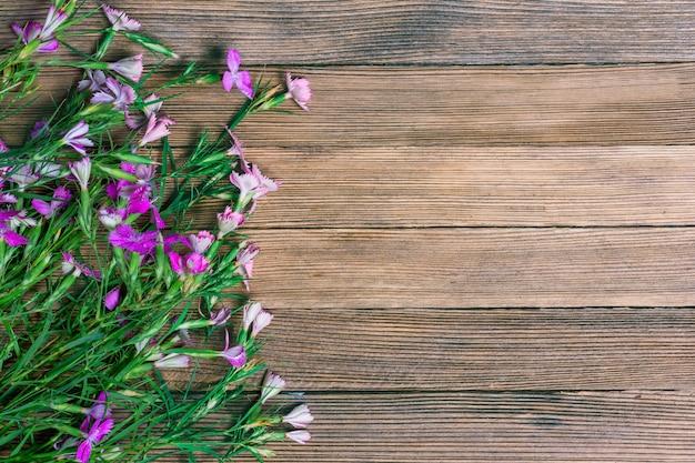 Bouquet d'oeillets sauvages dispersés sur un fond en bois avec espace de copie