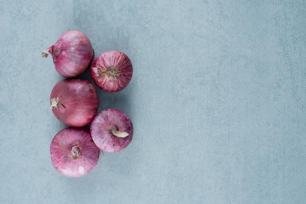 Bouquet d'oignons rouges sur marbre.