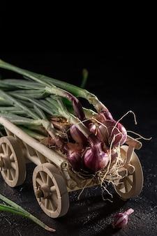 Bouquet d'oignons verts frais sur un chariot en bois