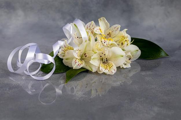 Un Bouquet D'orchidées Sauvages Sur Fond Clair Orné De Rubans. Fête Des Mères, Fête Des Femmes, Saint-valentin Ou Anniversaire. Baner. Copiez L'espace. Photo Premium