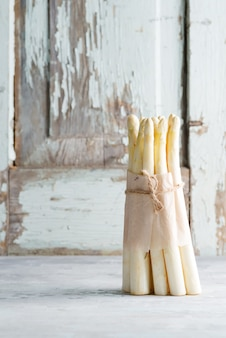 Bouquet organique naturel fraîchement cueilli de légumes asperges blanches sur un fond de pierre clair.